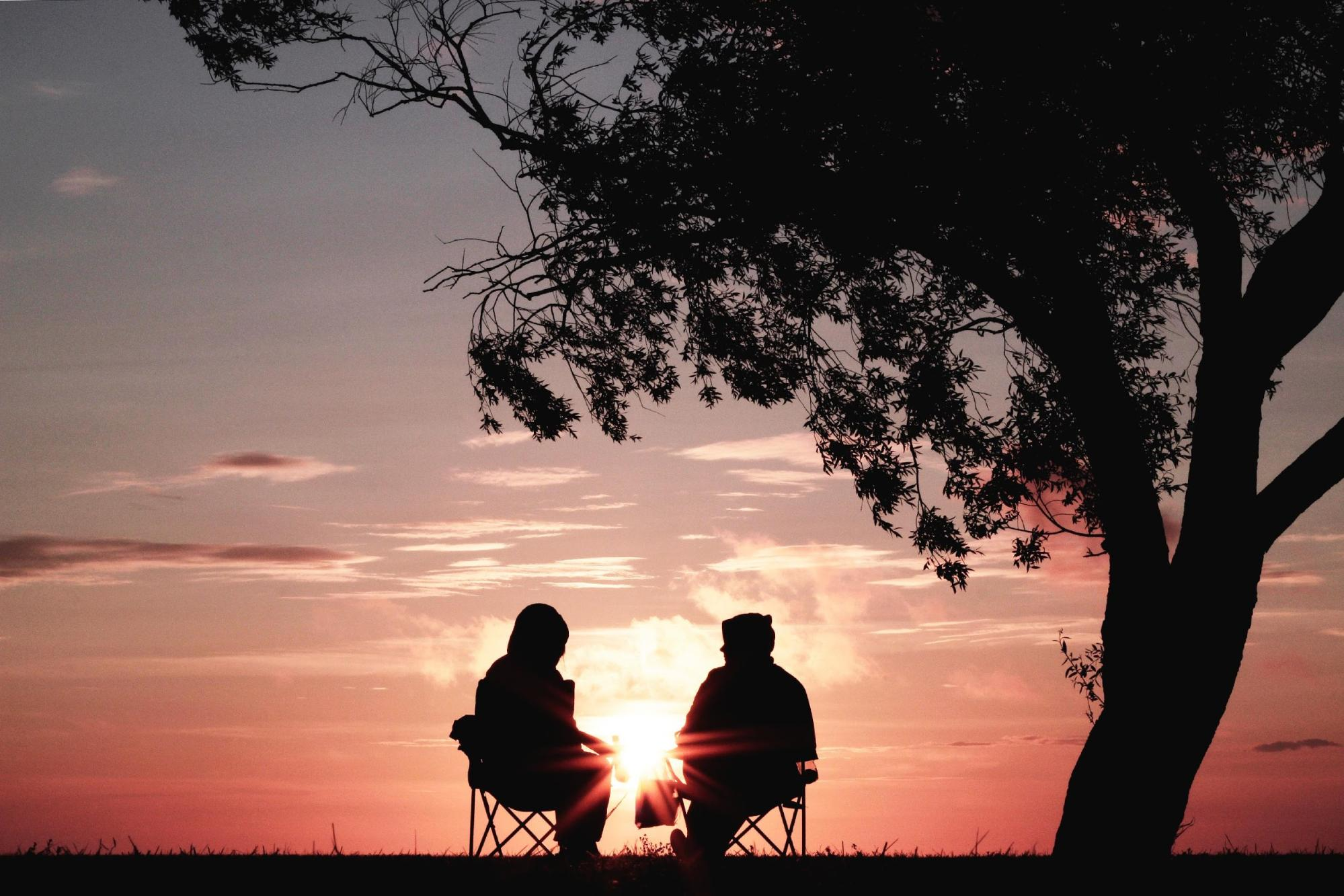 2 people relaxing without social media or phones at sunset